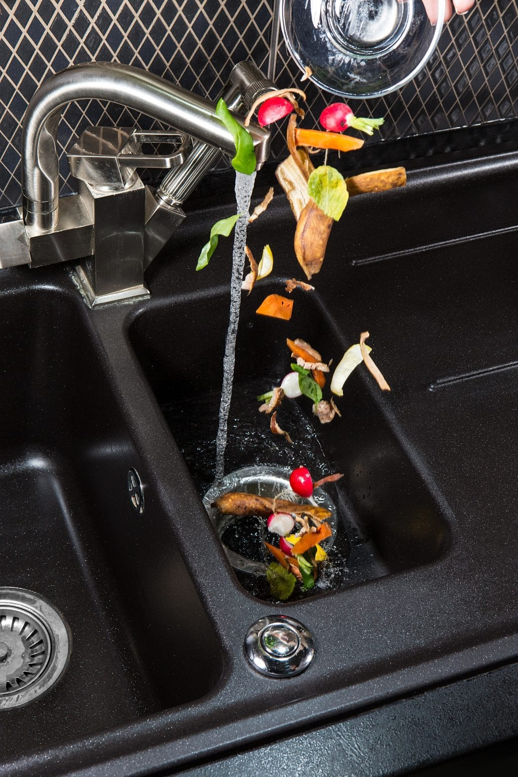 food material being dropped out of a metal bowl in to a sink garbage disposal